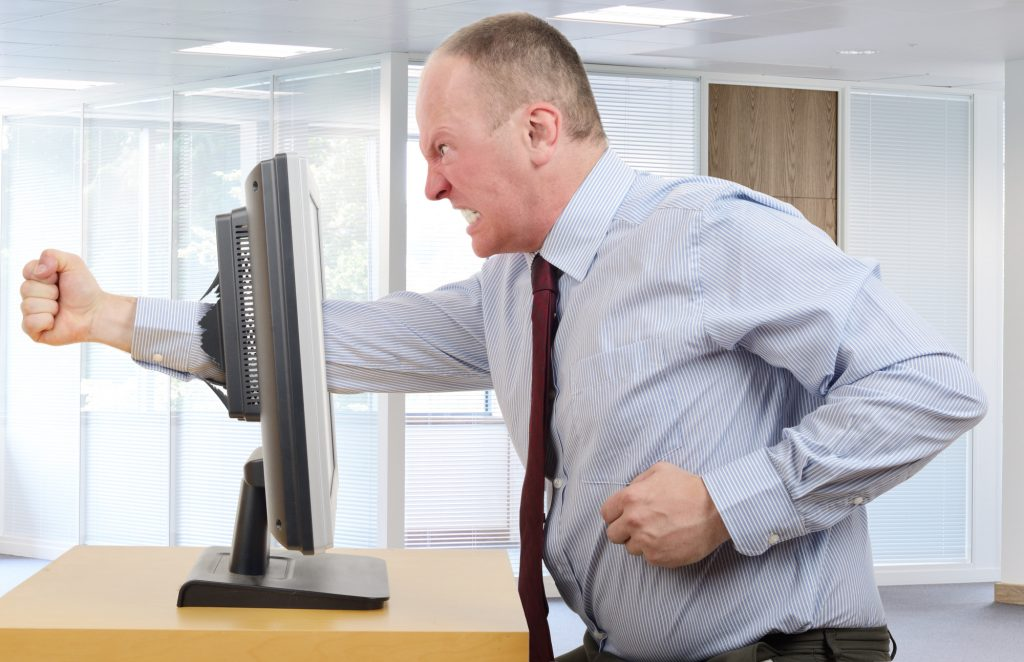 man with IT problems punching computer