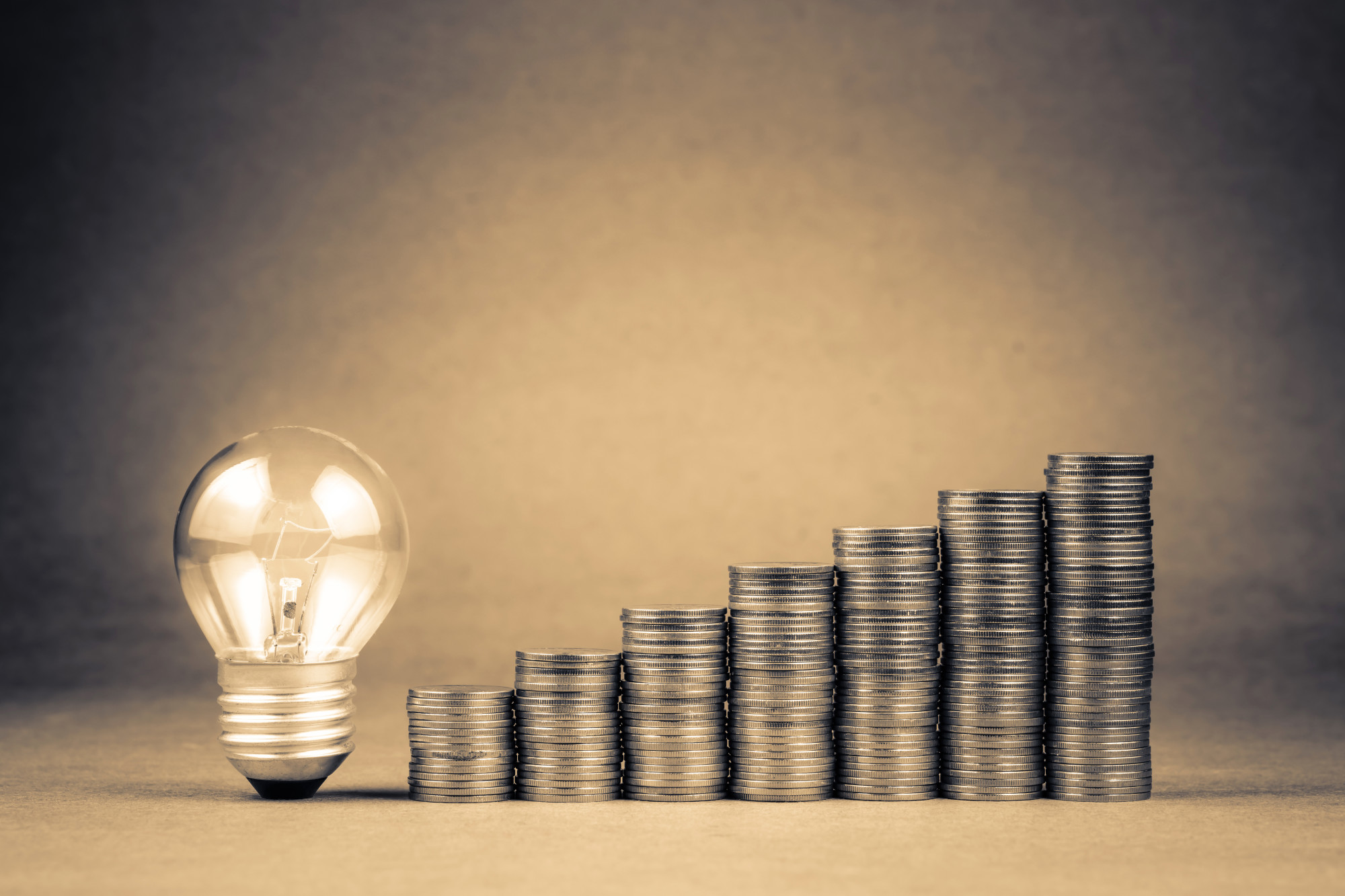 lightbulb and stacks of coins